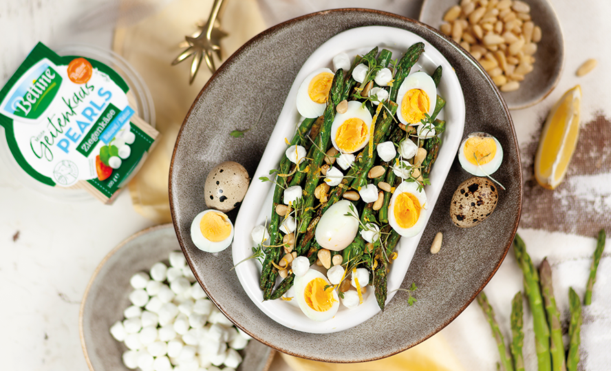 Warm salad with grilled asparagus, quail eggs, goat's cheese pearls and pine-tree-nuts