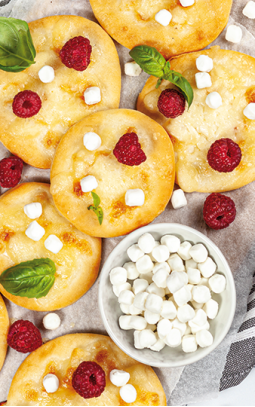 Mini pizzas with mozzarella, goat's cheese pearls and raspberries
